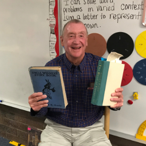IMAGE: Mr. McDivitt holds up books he reads to Ms. Summerset's 3rd grade class.