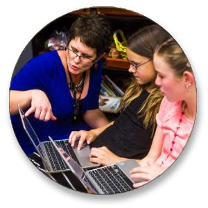 Educator instructing students on Chromebook assignment