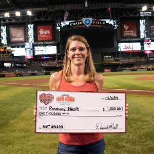 IMAGE: Rosemary Nicolls at Diamondback game holding $1,000 check.