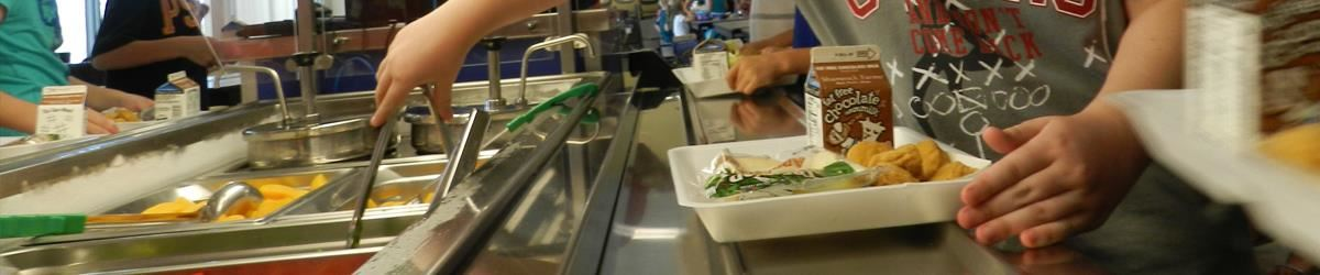Student using tongs to access fruit in lunch bar