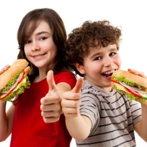 IMAGE: Female and male students eating sub sandwich and giving a thumbs up.