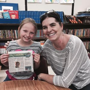 Ms. Baker with a student displaying award